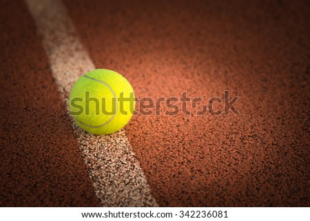 Close up of tennis ball on clay court./Tennis ball - stock photo