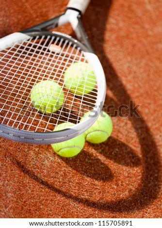 Close up of tennis racket and balls on the clay tennis court - stock photo