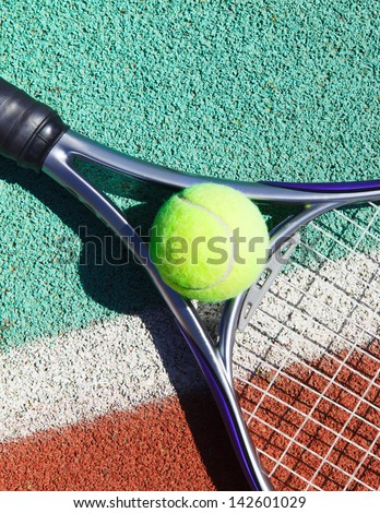 Close up of tennis racquet and ball on the clay tennis court - stock photo