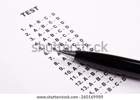 close up of test score sheet paper with answers and metal pen - stock photo