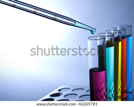 Close up of test tubes filled with color liquids and a pipette.