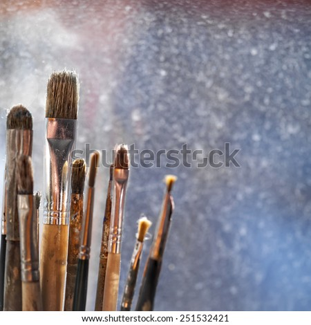 Close up of the artist paint brushes against window in artist studio, indoor shot with shallow depth of field - stock photo