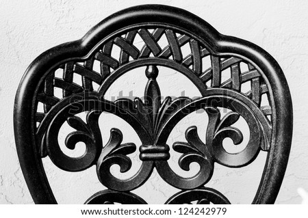 Close up of the back of a wrought iron chair in black and white against a grey stucco wall. - stock photo