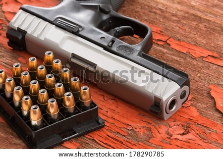 Close up of the barrel of a handgun and full rack of ammunition lying on a grungy wooden surface with red peeling paint conceptual of law enforcement, crime, violence and protection - stock photo