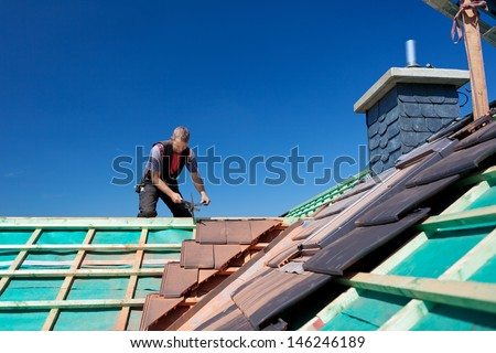 Close-up of the beams an unfinished roof with the roofer working in the background - stock photo