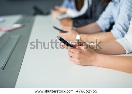 Close up of the business people texting on a mobile phones.