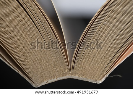 Close-up of the cover of a partially opened book on black