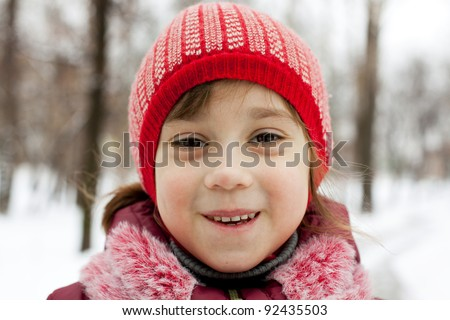 Close-up of the face a little girl in winter forest - stock photo