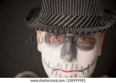 Close up of the face of a serious young man wearing creative skull makeup for Halloween dressed in a dark hat and cloak