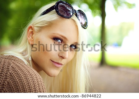 Close up of the face of a sexy blonde lady with sunglasses balanced on top of her forehead in a park. - stock photo