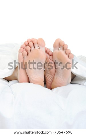 Close-up of the feet of a family on the bed. Isolated on white background