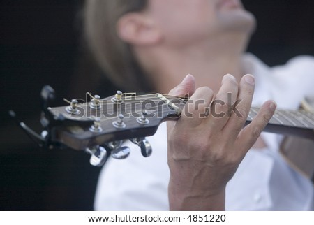 Close-up of the fingers of a guitar player during a performance.