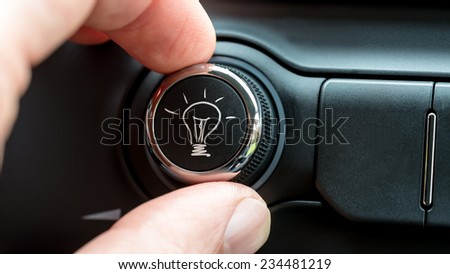 Close up of the fingers of a man turning a button with a hand-drawn illuminated light bulb in white on a piece of electronic equipment, conceptual of inspiration and innovation. - stock photo