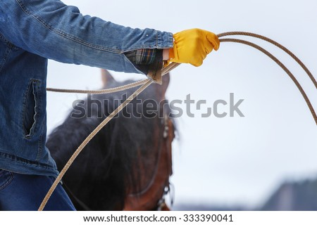 Close up of the hand of a cowboy on his horse holding a ranching rope. - stock photo
