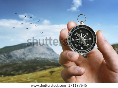 Close up of the hand of a man holding a magnetic compass over a landscape view as he uses it to navigate when exploring or travelling in the countryside - stock photo