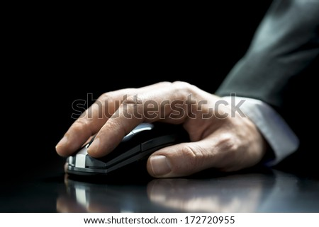 Close up of the hand of a man in a suit using a cordless computer mouse to navigate the internet on his computer - stock photo