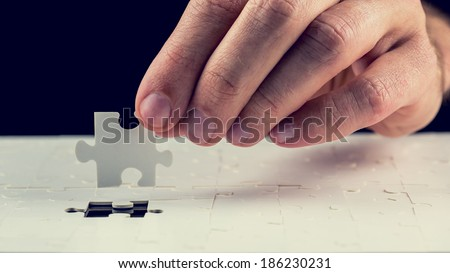 Close up of the hand of a man placing the last piece in place in a jigsaw puzzle conceptual of problem solving, finding a solution and meeting a challenge. - stock photo
