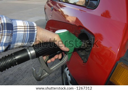 Close up of the hand of a motorist, filling his car with unleaded petrol on a garage forecourt. Beyond is the empty forecourt, but reflected in the car's bodywork is a housing estate and trees. - stock photo