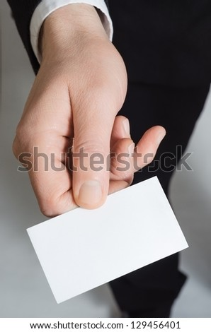 Close up of the hand of a suited business man, reaching forward to present a blank business card face upwards to the viewer. - stock photo