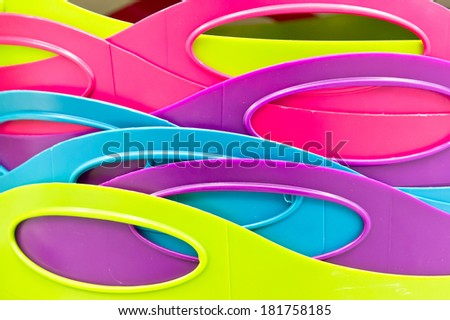 Close up of the handles of colorful plastic tubs