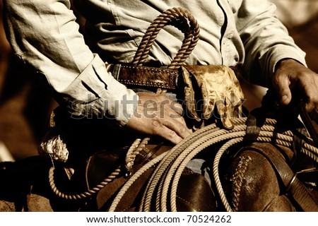 Close up of the hands and torso of an authentic working cowboy in the American West riding to work in sunset light (sepia/brown tint). - stock photo