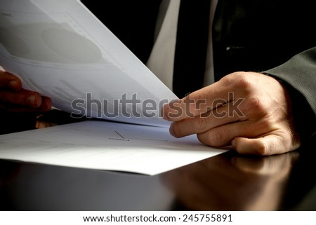 Close up of the hands of a business man analyzing business papers and holding a spreadsheet with statistics in his hand.