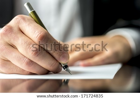 Close up of the hands of a businessman in a suit signing or writing a document on a sheet of white paper using a nibbed fountain pen - stock photo