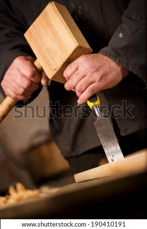 Close up of the hands of a carpenter or joiner using a chisel and wooden mallet to cut and shape a piece of wood in a woodworking workshop - stock photo