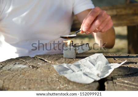 Close up of the hands of a male drug addict heating cocaine in a spoon over a flame from a lighter with a syringe in the foreground - stock photo