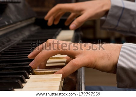 Close up of the hands of a male pianist playing music on an ivory keyboard on an old piano as he practices for a performance - stock photo
