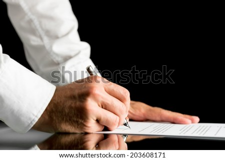 Close-up of the hands of a man wearing white shirt while signing with a pen an official paper document or agreement, placed on a black reflective table, with copy space on black background. - stock photo