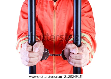close up of the hands of a prisoners in jail with handcuffs on a white background with clipping path - stock photo