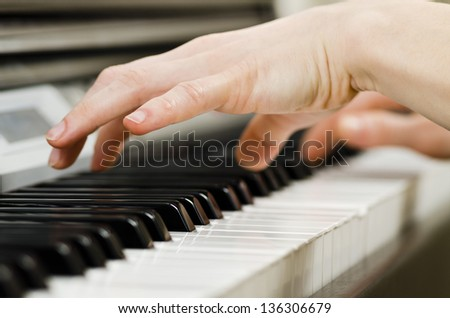 Close up of the hands of a young woman playing piano - stock photo