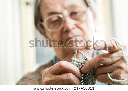Close up of the hands of an elderly woman knitting. - stock photo