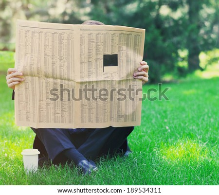 Close up of the hands of the businessman with a newspaper. Outdoors - stock photo