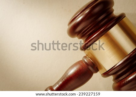Close up of the head of a judge or auctioneers wooden gavel with a brass band around it and copyspace - stock photo