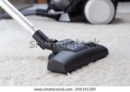 Close up of the head of a modern vacuum cleaner being used while vacuuming a thick pile white carpet - stock photo