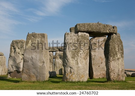 Close-up of the massive circle of stones that make up the world famous landmark and World Heritage Site Stonehenge on Salisbury Plain, Wiltshire, England. Blue sky with white fluffy clouds. - stock photo