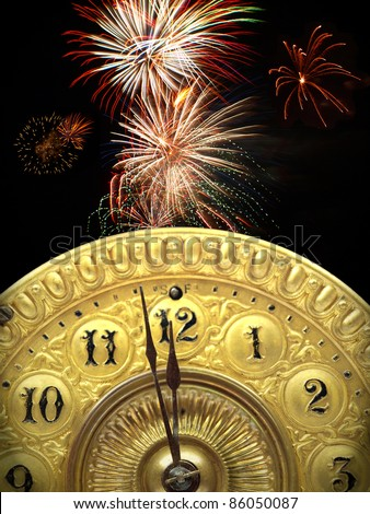 Close up of the minute hand of a antique clock face about to strike 12 o-clock midnight to start the new year with fireworks in the background. - stock photo