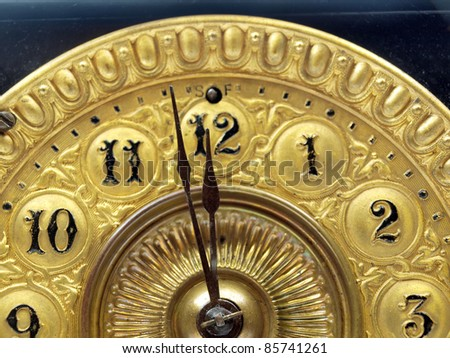 Close up of the minute hand of a black and gold antique mantle clock about to strike 12 o-clock. - stock photo