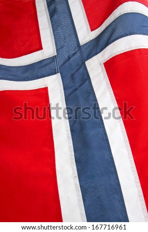 Close up of the National flag of Norway in Scandinavia, Europe. With a blue & white cross over a red background.