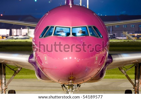 Close up of the nose of a violet airbus parked at night. - stock photo