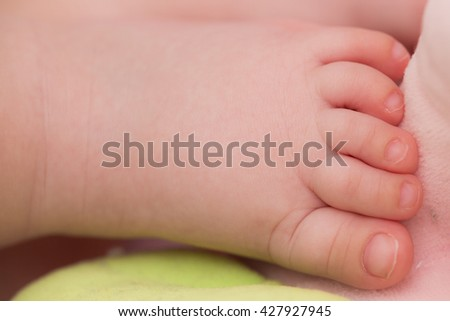 Close-up of the nude left foot of a baby that is sleeping.
