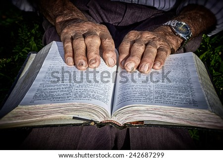Close-up of the old hands placed on a book, proving the labor of life. - stock photo