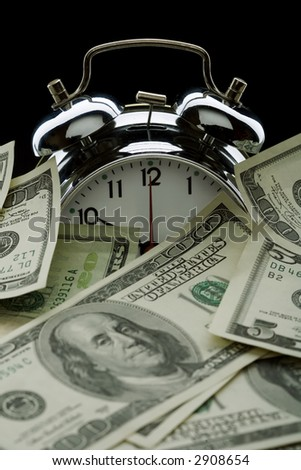 close up of the oldfashioned alarm clock with money - stock photo