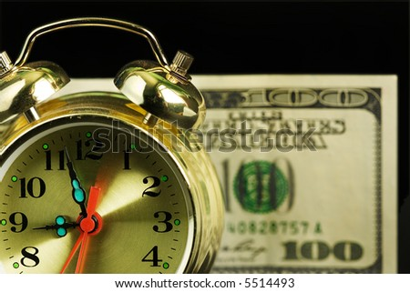 Close up of the oldfashioned alarm clock with money. Shallow depth of field. - stock photo