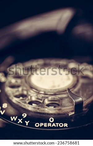 Close up of the operator dial on a black vintage telephone with filtered effect - stock photo