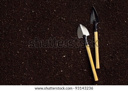 Close-up of the organic soil and spade - stock photo
