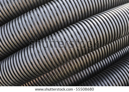 Close up of the pattern formed by a coil of black plastic pipework, suitable as abstract background. - stock photo