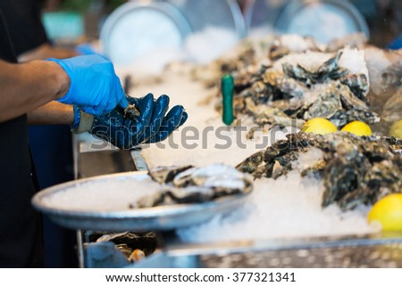 close-up of the process of shucking oysters at the restaurant, shallow DOF on hands - stock photo